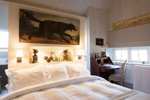 Schlafzimmer mit antikem Sekretär und Raumteilerwand am Betthaupt
