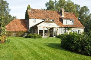 Traditional country house with striped green lawn