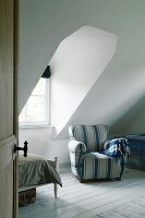 Comfortable blue-striped armchair next to dormer window