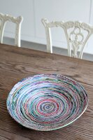 Colourful hand-crafted paper dish on wooden table