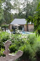 Summer house and pool in summery garden with mature trees
