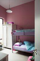 Bunk beds and pink walls in children's bedroom
