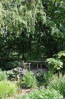 Lauschiger Gartenplatz mit Holzmöbeln unter Laubbäumen
