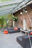 Wintergartenanbau an rustikaler Ziegelfassade mit grauen Designer-Loungemöbeln und orangefarbenen Farbakzenten