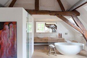 Badezimmer hinter Glaswand in ausgebautem Dachgeschoss mit rustikaler Fachwerkkonstruktion