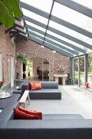 Designer-Lounge in Wintergartenanbau mit Einblick in Essbereich von restauriertem Landhaus