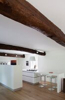 Rustic beams above counter in white designer kitchen