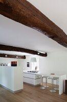 Rustikale Balken über weißer Designerküche mit Küchentheke