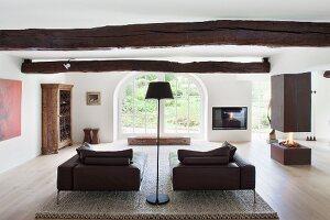 Loungebereich mit Kaminfeuer unter Kaminabzug in Designerambiente mit rustikalem Flair