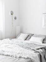 Crumpled pale grey bed linen in white bedroom