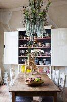 Aufgehängte Glasvasen mit Blumendekoration über Holztisch mit künstlerischen Vasen und vor vollem Geschirrschrank