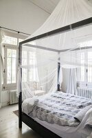 Black four-poster bed with mosquito net in white bedroom
