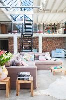 Comfortable pastel lounge area in front of black metal staircase leading to gallery