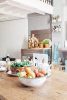 Stainless steel kitchen furnishings and fruit bowl on rustic dining table below white gallery in loft apartment