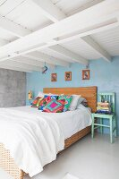 Double bed with rattan frame and vintage wooden chair below white wood-beamed ceiling