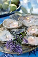 Tealights in oyster shells and lavender decorating table