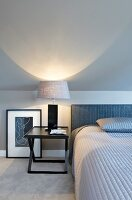 Elegantes Schlafzimmer mit schwarzem Nachttisch und Nachttischlampe
