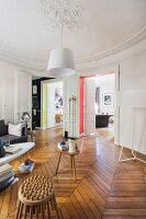 Stucco ceiling and retro ambiance in living room of renovated period apartment