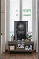 Towels in modern bathroom cabinet with portrait of woman on top in front of French windows