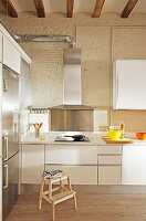 White kitchen counter with extractor hood in high-ceilinged, loft-style interior