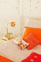 Orange pillows on bed and retro bedside lamp