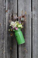 Blumen in alter Emaillekanne an Holztür
