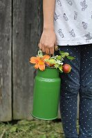 Girl holding old milk churn full of flowers