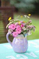 Wildblumen im Keramikkrug auf Gartentisch