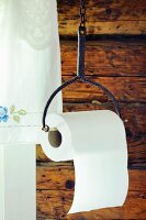 Toilet roll hung from old iron holder against rustic wooden wall