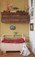 Dog ornament in front of vintage wooden bench below antique wall-mounted cabinet in hallway