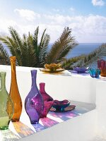 Colourful glass vases and bowls on white wall with view of sea