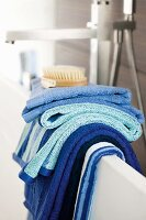 Towels in shades of blue hanging over edge of bathtub
