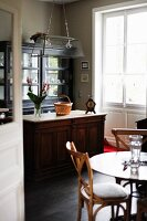 Vintage dresser in front of crockery in glass-fronted cabinet in traditional interior