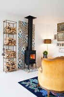 Firewood on shelves next to wood-burning stove on strip of colourful tiles on wall and floor