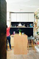 Weiße Oberschränke und Küchentheke vor Wand mit Retro Zeitungsausschnitten tapeziert