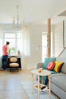 Wohnzimmer mit Couch, Holztisch und antikem Stuhl vor Fenster in restauriertem Altbau