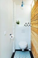 Toilet with rustic, reclaimed board wall and ornate floor tiles