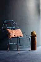 Delicate metal chair with leopard-print cushion against dark wall