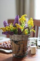 Gelb-violetter Blütenstrauss in Drahtkorb als Tischdekoration