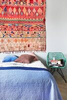 Colourful ethnic rug on wall above bed with blue bedspread and various scatter cushions