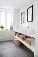 White countertop sinks below black-framed mirrors in minimalist bathroom