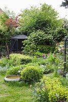 Flowering spring flowers and birdbath in idyllic garden