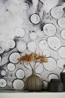 Vase of dried flowers against black and white modern artwork