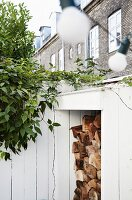 Stacked firewood in white wood-clad niche topped by climbing plant in front of traditional brick terrace façade