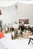 Arrangement of ornaments and DIY candle lanterns on cosy wooden terrace