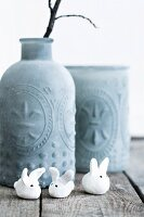 Tiny polymer clay rabbit in front of vase with structured surface