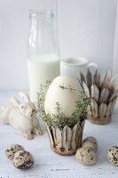 Osterei im Metallkrönchen mit Thymian neben Wachteleiern
