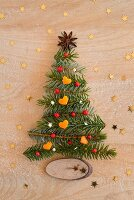 Christmas tree made from fir twigs laid on wooden surface