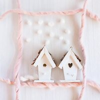 Small house ornaments surrounded by frame made from pink wool on white surfae