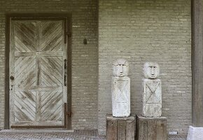 Two figures on wooden plinths next to wooden door in brick wall